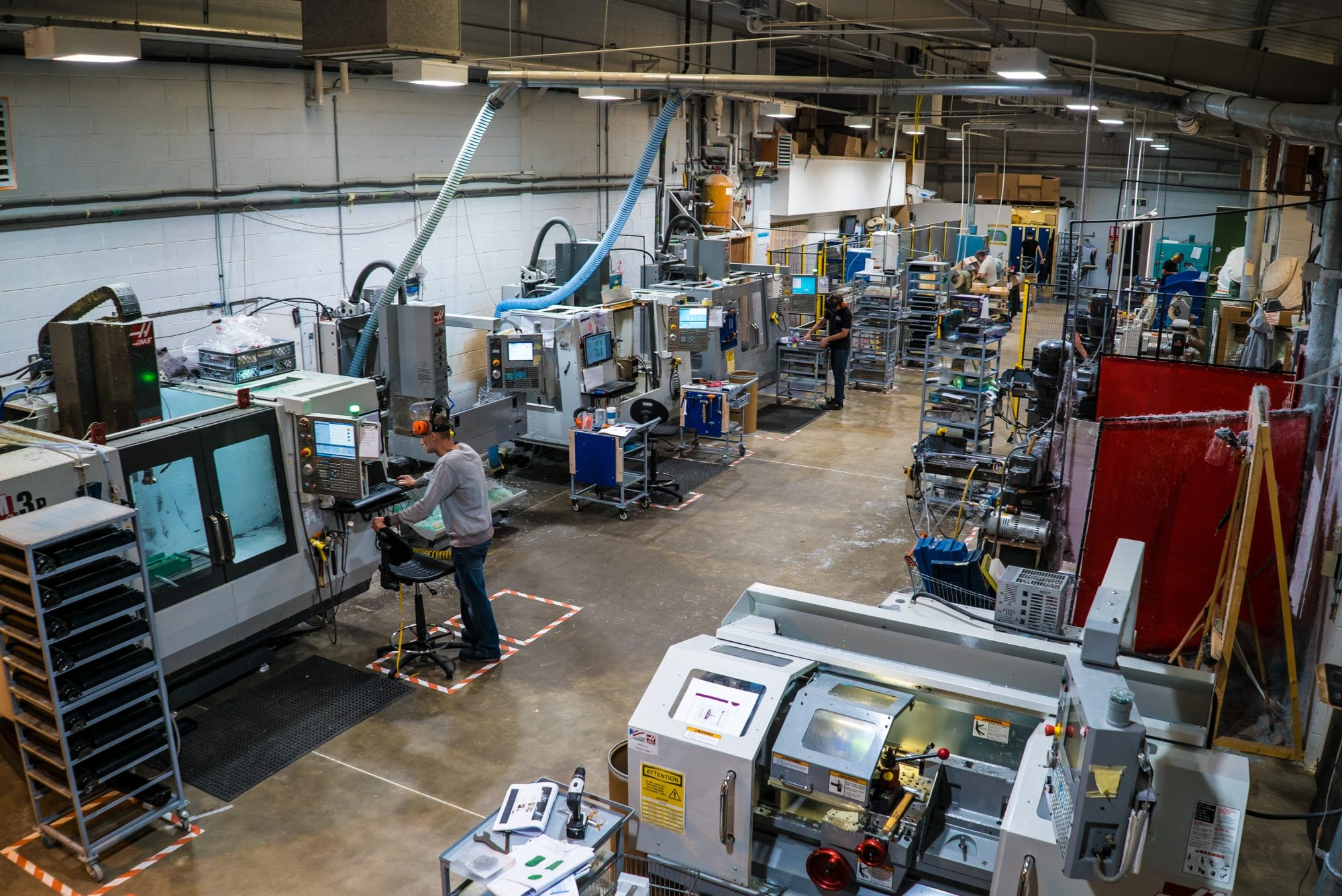 a large machine shop with CNC machine and operators