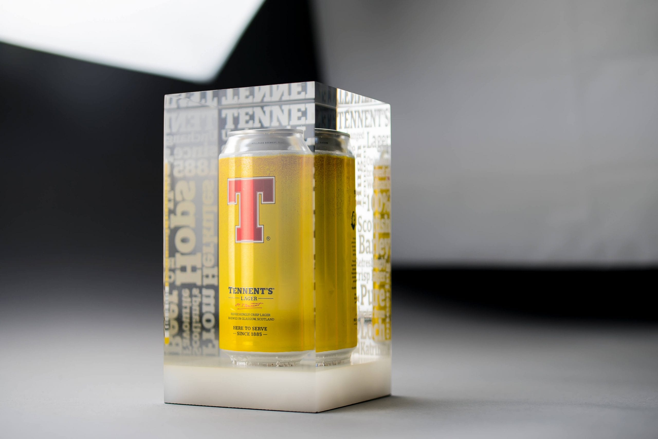 A can of Tennents lager encapsulated in clear acrylic with etched lettering on the back